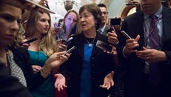 Sen. Susan Collins is surrounded by reporters on Capitol