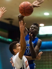 In a 2014 Governor's Challenge game, Decatur's Tyree Henry swats away a shot from Delmar's Shane Leatherbury.