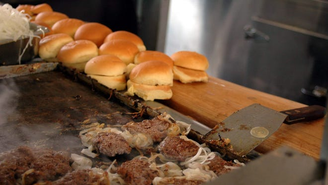 The White Manna Hamburgers restaurant in Hackensack was originally a booth at the Worlds Fair in Queens in 1939. It was moved from Queens to Hackensack in 1946. Some rumors say that White Castle was based on this burger joint. Here burgers cook on the grill.