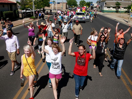 Marchers in the Pride parade head down Main Street on Saturday through downtown Farmington.