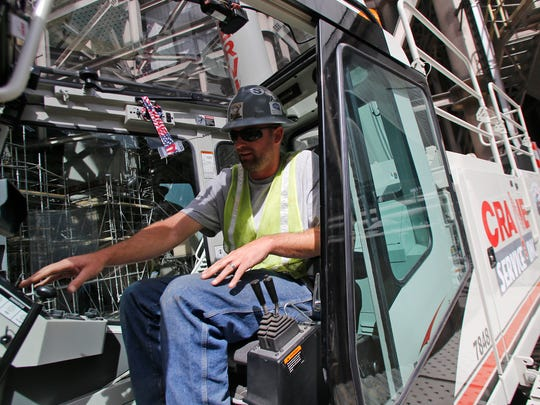Crane operator Scott Brown on Wednesday talks about the controls inside a crane's cabin at a work site at the San Juan Generating Station in Waterflow.