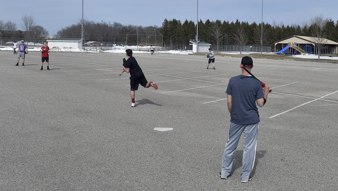 The Sevastopol High School baseball team finds a dry spot to practice in the parking lot adjacent to its home field Monday. Coach Jason Marggraf said the field is still too wet to practice.