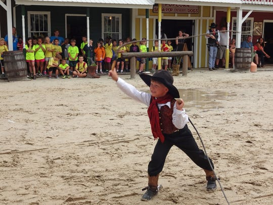 With one whip in the air and the other one ready to go, Clay Karson, 6, entertains guests at Frontier Town.