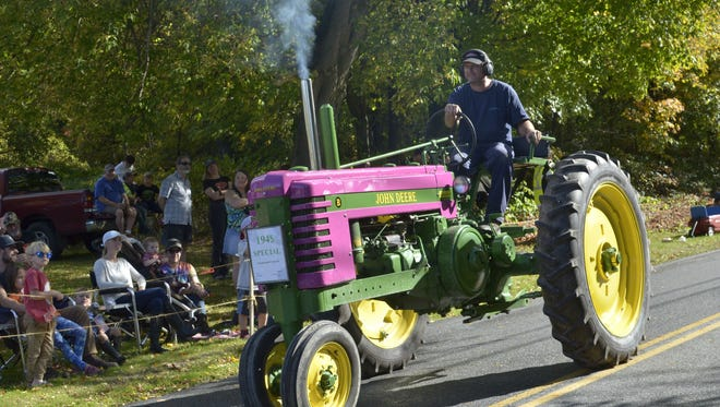 Smoke comes out of a pipe on the front of the tractor of a participant in the annual East Charlotte Tractor Parade on Sunday, Oct. 8, 2017.