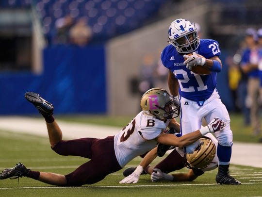 Memorial's Kenyon Ervin (21) is tackled by Brebeuf