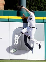 Center fielder JaCoby Jones of the Detroit Tigers reaches over the fence to catch a ball hit by Adrian Beltre of the Texas Rangers during the sixth inning Saturday.
