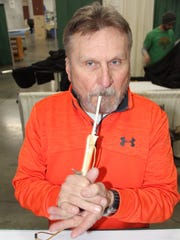 Loren Voss of Fond du Lac, Wis., demonstrates a series of yelps with a call made from the wing bones of a wild turkey.