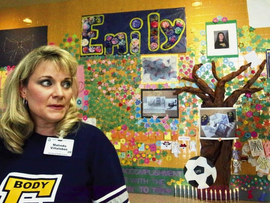 Eastwood Middle School Principal Malinda Villalobos speaks Wednesday in front of a large wall decorated by students in memory of Emily Rose Nevarez. Emily, who was an eighth-grader at the school, was shot and killed by her father, who then turned the gun on himself Tuesday in far East El Paso. The memorial will remain up through the end of the school year, Villalobos said.