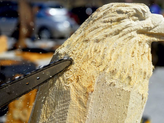 """Chain saw carver Paul Waclo, of Springfield Township, works on an eagle sculpture outside Brown's Orchards & Farm Market on Saturday. Waclo owns seven chain saws, ranging from one with a 36 inch bar to a """"dime tip"""" chain saw used for fine details."""