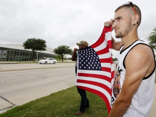 Conner McCasland, right, and Joseph Offutt hold a U.S. flag across the street from the Curtis Culwell Center, Tuesday, May 5, 2015, in Garland, Texas. A man, whose social media presence was being scrutinized by federal authorities, was one of two suspects killed in the Sunday shooting at this location that hosted a cartoon contest featuring images of the Muslim Prophet Muhammad. The Islamic State group on Tuesday claimed responsibility for the attack. (AP Photo/LM Otero)