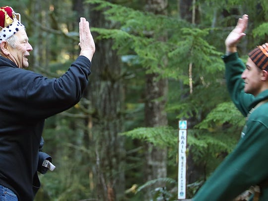Volunteer Bob Mathisrud (left) gives high-fives to the runners Saturday as they head down the first trail turn-off of the first loop for the Green Monster Duathlon on Green Mountain.