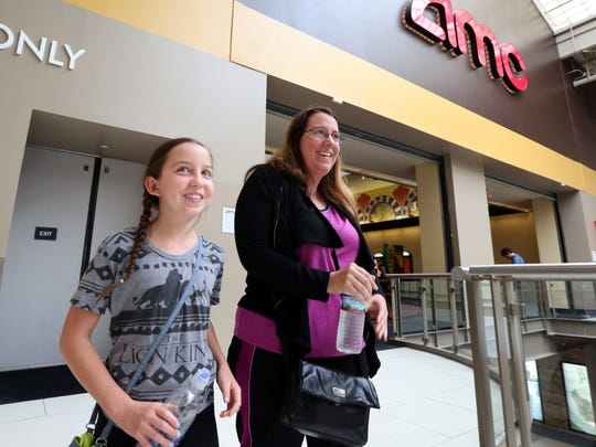 Kim Szechter and her daughter, Talia, 11, of Sedona, Arizona get tickets for a movie at the Palisades Center mall in West Nyack June 28, 2017.