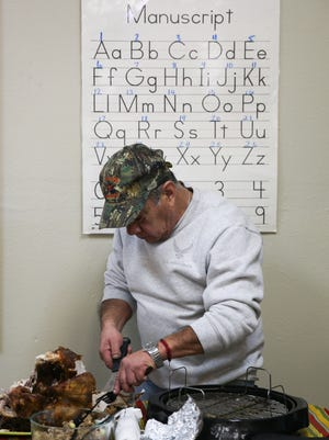 Jesus carves the turkey for the Thanksgiving celebration Nov. 16 at the Adult Literacy Council of the Concho Valley.