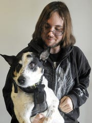 Anthony Downey holds his service dog, Whitey, who has