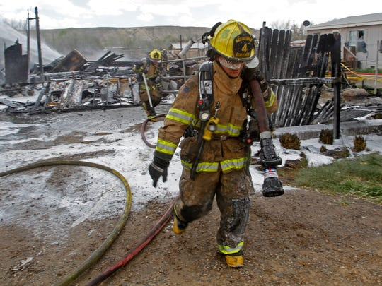 A San Juan County Fire Department firefighter moves a hose while extinguishing a fire on Saturday in Kirtland.
