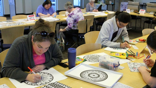 Liz Ricci, left, and Jasmine Htoon take part in an adult coloring session at the Farmington Public Library. The monthly event returns on Monday.