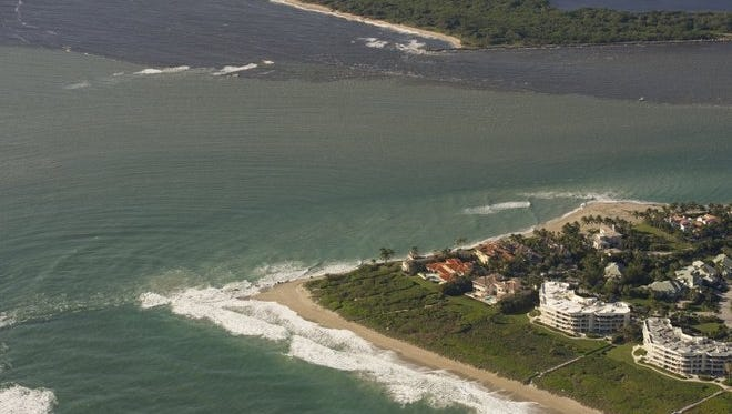 Murky waters from Lake Okeechobee discharges flow south Feb. 11 from the St. Lucie Inlet.