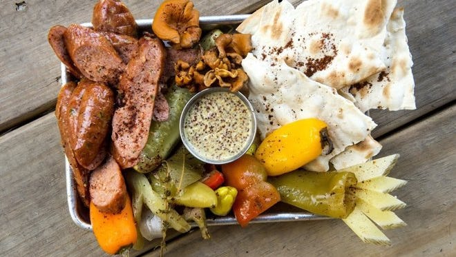 This sausage plate with chanterelle mushrooms is available Loflin Yard bar and restaurant south of downtown Memphis. It is served with a variety of peppers and pickles and oversized toasted crackers.The space features an outdoor beer garden and lawn games, two bars, patio dining, live music and a full menu.