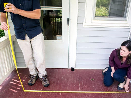 Jon Clancy, left, and fiancee Susanna Smith measure the back deck of their future North Asheville home on Edgewood Road on Monday.