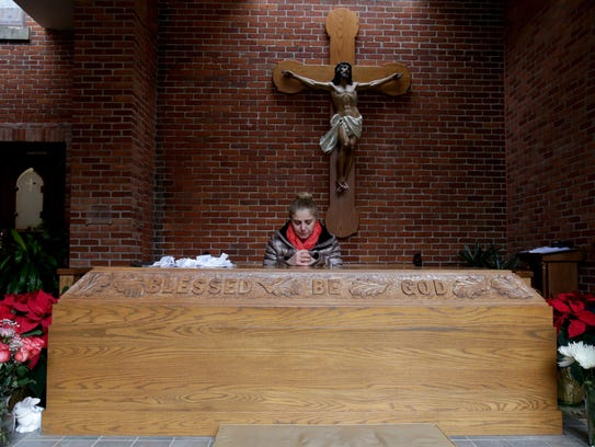 Vivian Hurmoz of Troy kneels and prays at the tomb of Father Solanus Casey just outside of the Solanus Casey Center church.