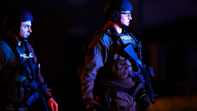 On Monday, Dec. 15, 2014, Police gather near a home in Pennsburg, Pa., where suspect Bradley William Stone is believed to have barricaded himself inside after shootings at multiple homes.