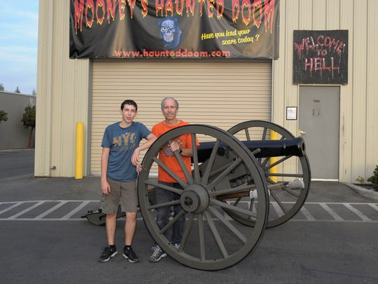 Rollin George, right, and his son Conner George, 16, of Visalia, pose next to their Civil War-replica cannon on Wednesday, October 15, 2014 in front of Mooney's Haunted Doom in Visalia.