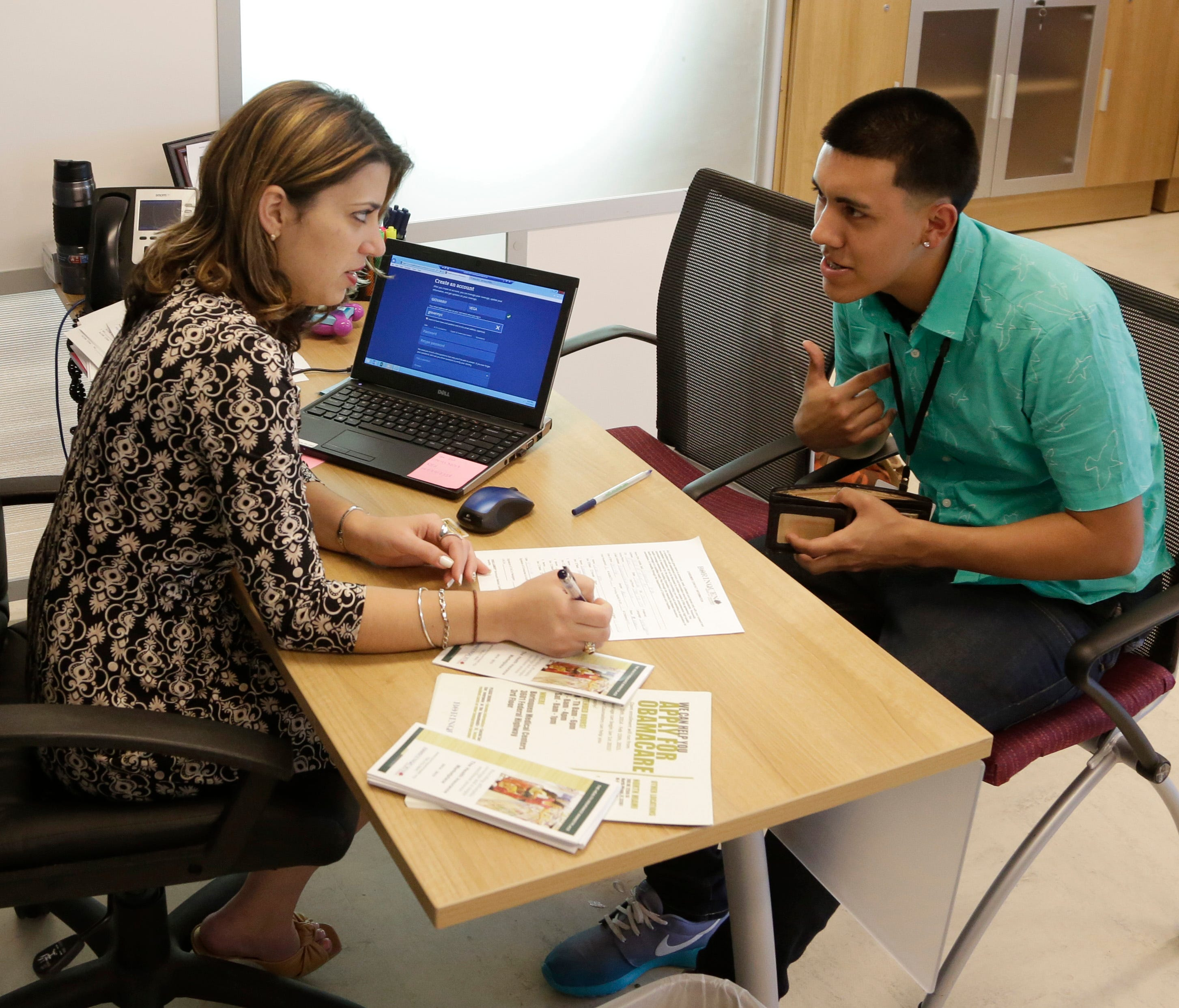 This file photo shows Navigator Dianelys Dominguez, left, assisting Giovanny Vega, 18, of Miami, right, sign up for health insurance under the Affordable Care Act, Monday, Nov. 17, 2014, at the Borinquen Medical Center in Miami.