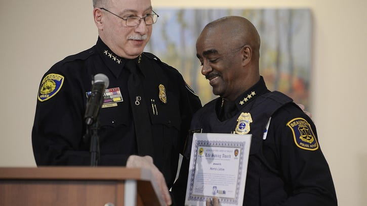 Dearborn Police Chief Ronald Haddad left, presents Morris Cotton, Beaumont Health's deputy director of system security, with a citation for his efforts.
