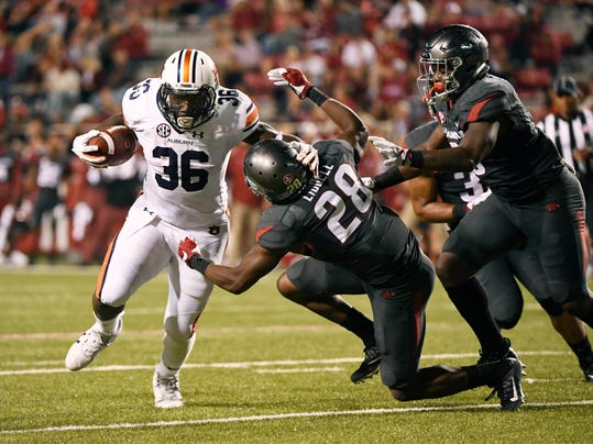 Auburn running back Kamryn Pettway (36) slips past Arkansas defender Josh Liddell (28) and De'Jon Harris (8) as he runs for a touchdown during the second half of an NCAA college football game in Fayetteville, Ark., Saturday, Oct. 21, 2017. (AP Photo/Michael Woods)