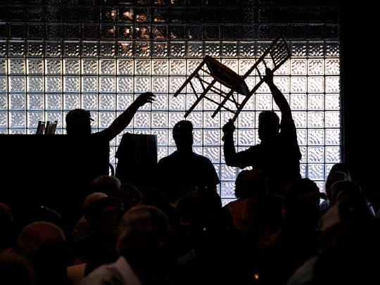Volunteers are silhouetted against the glass brick wall of the Reunion Center in Comanche on June 14, 2018, as they pass chairs overhead for the additional people coming in the door. The Comanche County Taxpayers Co-op held a meeting to discuss how to protest the new valuations issued earlier in the month by the county's Central Appraisal District.