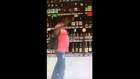 Video taken Oct. 8 shows a woman apparently putting a bottle in her purse, then doing a popular dance.