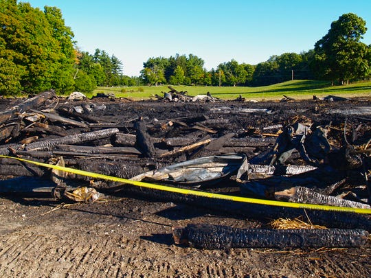 Ashes, bits of charred wood and twisted metal are all that remain of the Old Dairy Barn at Shelburne Farms on Monday, Sept. 12, 2016. The historic structure caught fire early Sunday morning.