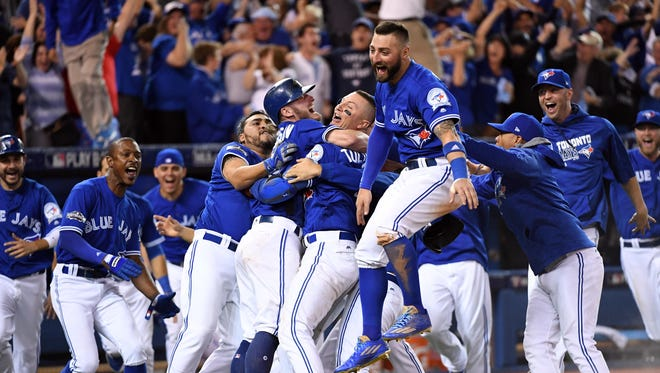 Josh Donaldson celebrates with teammates after scoring the winning run in the 10th inning.