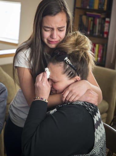 Joy Rangel is hugged by her daughter Bella as she talks
