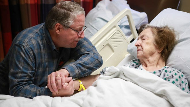 Baptist Health chaplain Jim Ivey of Louisville, Ky., left, holds hands with patient Ruth Link, 92, in her hospital room while they pray May 4, 2015.