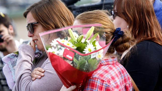 A woman identified as the fiancée of a shooting victim is comforted by friends as she leaves flowers Thursday near the Inland Regional Center in San Bernardino, Calif.