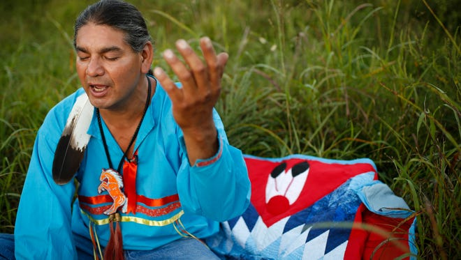 """Matt Black Eagle Man, a Radcliff, Ky resident originally from the Long Plain First Nation reserve in Manitoba, Canada, sings native songs in prayer in a field near his home. Black Eagle Man and others will hold an event at Louisville's Cox's Park on Saturday, Oct. 1 from 2-4pm for a water blessing and to gather supplies to take to protesters at Standing Rock. """"The idea of domination for us is a foreign concept, because we know we have a responsibility to find balance in this world,"""" Black Eagle Man said. As the North Dakota camp prepares for the winter ahead, Black Eagle Man will be making a supply run and is in need of more tarps, blankets and other items to aid protesters. Sept. 20, 2016"""