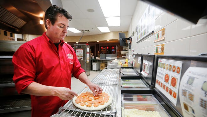John Schnatter, founder of Papa John's Pizza makes a pizza in the kitchen of his company's headquarters.