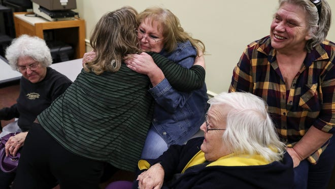 Pleasant Ridge residents embrace during a neighborhood meeting following a meeting at City Hall on the day that a ruling in their favor was issued in their case against the city of Charlestown. Dec. 4, 2017