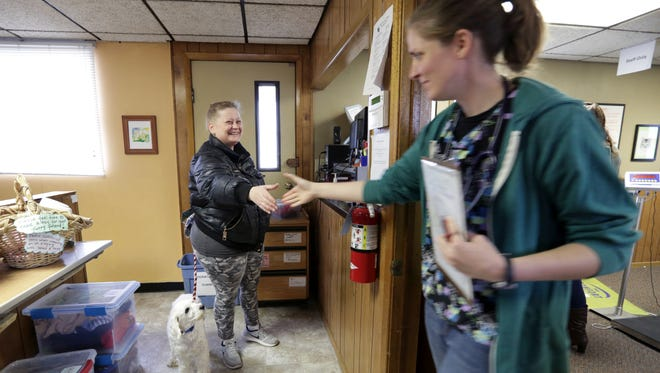 Heather Corkery, of Madison, left, meets Bridget Holck, a fourth-year veterinary student at UW-Madison, before heading to a room to examine Corkery's dog, Apple, during a follow-up visit for an ear infection at WisCARES, a free pet care clinic run partly by veterinary students, in Madison, Wis., Thursday, Nov. 16, 2017.