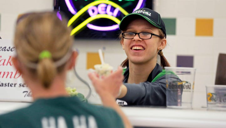 Kaela Lundeen offers a customer a food sample while working in the deli at Festival Foods on Sunday, September 11, 2016 in Appleton, Wisconsin. She is saving money to attend Fox Valley Technical College.