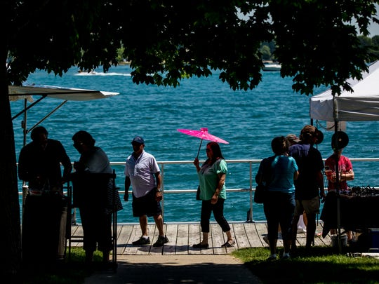 People walk among dozens of booths along the waterfront during the St. Clair Art Fair Saturday, June 25, 2016, in St. Clair.
