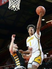 Woodbury's Aaron Estrada takes the ball to the hoop