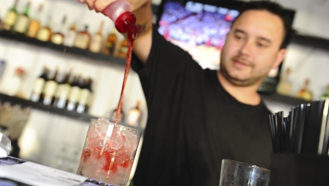 Bartender Tom Benson mixes a drink for a customer at Meskla on the Cove in Tamuning on May 9.