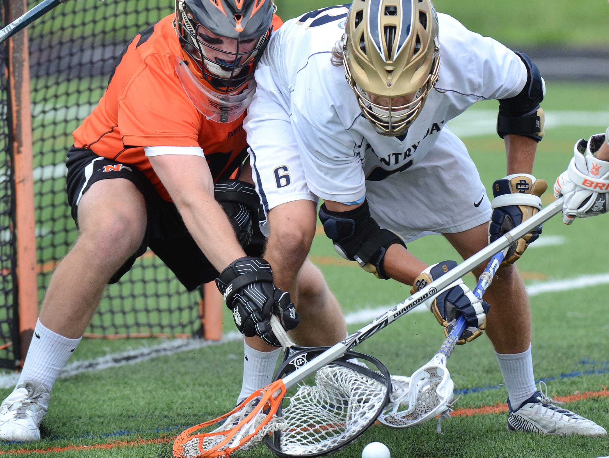 Northville goalie Alex Justice (left) battles with Country Day's Nick Martin for control of the ball in the crease during the May 26 boys lacrosse regional semifinal.