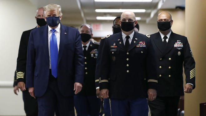 "FILE - In this July 11, 2020, file photo President Donald Trump, foreground left, wears a face mask as he walks with others down a hallway during a visit to Walter Reed National Military Medical Center in Bethesda, Md. On Tuesday, July 21, Trump professed a newfound respect for the protective face masks he has seldom worn. ?Whether you like the mask or not, they have an impact,"" he said. ""I?m getting used to the mask,? he added, pulling one out after months of suggesting that mask-wearing was a political statement against him."
