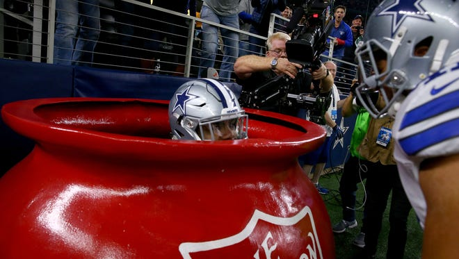 Ezekiel Elliott of the Dallas Cowboys celebrates after scoring a touchdown by jumping into a Salvation Army red kettle during the second quarter against the Tampa Bay Buccaneers at AT&T Stadium on Sunday.