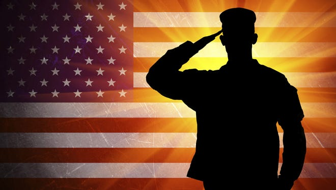Saluting Army soldier on American flag background.