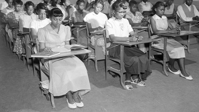 """Henrietta Hilton, front left, daughter of tenant farmer William Hilton, and her fellow students, are seen in their ninth grade classroom in Summerton, S.C., June 4, 1954. The classroom is in a newly built brick building that adjoins to the old wooden structure, which is the center of a controversy which led to one of four cases involving """"separate but equal"""" facilities for blacks and whites."""