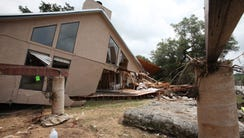 A flood damaged home sits beside its foundation on